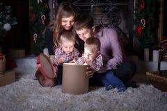 Праздник Кристмас Семья раскрывает волшебную коробку с подарком Стоковые Фото