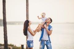 Праздник семьи в природе 3 люд, мама, папа, дочь проводят один год на море скалы обозревая Молодые люди игры, вокруг и стоковые изображения rf