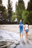 Праздник семьи около моря 2 взрослого в одеждах джинсов с ребенком в их оружиях идут вдоль песчаного пляжа от позади стоковое изображение
