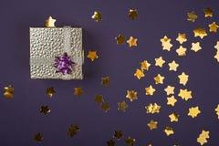 Праздничная золотая коробка на пурпурной предпосылке со сверкнает звезды Праздничная предпосылка для вашего проекта горизонтально стоковые изображения