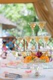 Праздничная сервировка стола с плодоовощ и рюмками с шампанским розы перлы приглашения украшения декора карточки boutonniere пред Стоковое Изображение