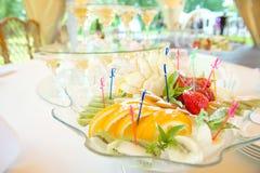 Праздничная сервировка стола с плодоовощ и рюмками с шампанским розы перлы приглашения украшения декора карточки boutonniere пред Стоковое фото RF