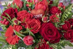Праздничный букет разнообразие красных цветков и сердце с любовью надписи на другие праздники Валентайн день и стоковое фото