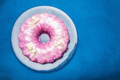 Праздничный круглый торт с розовой замороженностью на голубой предпосылке стоковое фото