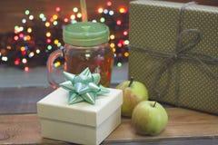 Праздничный натюрморт с белым giftbox, стеклянная чашка чаю с крышкой, зеленые яблоки, fairy света Стоковая Фотография