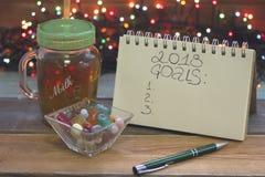 Праздничный натюрморт с стеклянной ясной чашкой чаю с крышкой, надписью 2018 целей, шаром конфет, fairy светов Стоковые Изображения
