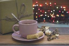 Праздничный натюрморт с чашкой чаю, подарочной коробкой и fairy светами Стоковые Фото