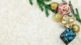 праздничный оборачивать подарка с смычком цвета золота с шариками игрушек Стоковые Изображения