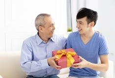 праздновать и сын семьи давая подарок к отцу стоковые фото