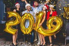Праздновать партию Нового Года Группа в составе жизнерадостные маленькие девочки в красивом нося золоте нося покрасила 2019 и стоковое изображение