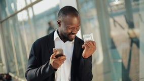 Праздновать счастливого Афро-американского бизнесмена веселя смотрящ сотовый телефон и держащ большую сумму денег в его акции видеоматериалы