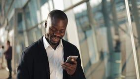 Праздновать счастливого Афро-американского бизнесмена веселя смотрящ сотовый телефон и держащ большую сумму денег в его сток-видео