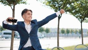 Праздновать счастливого молодого бизнесмена веселя смотрящ smartphone Хорошие новости в деле Успех и достижение акции видеоматериалы