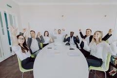 праздновать успех Группа в составе молодые бизнесмены поднимая их оружия и смотря счастливый пока сидящ вокруг стола совместно стоковые фото