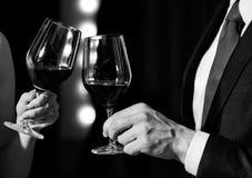 праздновать успех приветственные восклицания, пары clink стекла с красным вином стоковое изображение