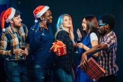 Празднующ Новый Год совместно Группа в составе красивое молодые люди в шляпах Санты стоковая фотография rf