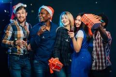 Празднующ Новый Год совместно Группа в составе красивое молодые люди в шляпах Санты стоковое фото