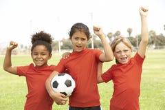 празднующ футбол девушки объениняются в команду детеныши Стоковое фото RF