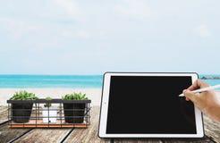 Праздники пляжа, сочинительство руки на цифровой таблетке с цветком кактуса в горшке, на деревянном столе Стоковые Фото
