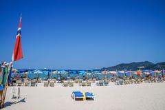 Праздник пляжа лета на пляже Patong ослабляет в солнце на loungers солнца под красивым зонтиком предпосылки перемещения Стоковые Фото