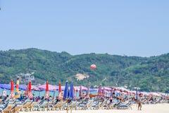 Праздник пляжа лета на пляже Patong ослабляет в солнце на loungers солнца под красивым зонтиком предпосылки перемещения Стоковое Изображение RF