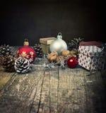 Праздничные подарки с коробками, безделушками, конусами сосны, грецкими орехами на деревянной предпосылке Стоковое фото RF