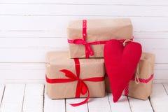Праздничные подарочные коробки и красное декоративное сердце на белом деревянном bac Стоковые Фотографии RF
