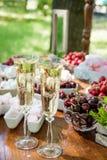 Праздничные рюмки сервировки стола с шампанским, плодоовощ и зефирами Стоковое Изображение