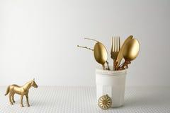 Праздничный золотой нож столового прибора и ложка в белой бутылке, светлая предпосылка вилки Стоковая Фотография