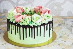 Праздничный торт при розы сделанные из сливк на белой деревянной предпосылке Стоковое Изображение RF