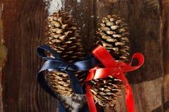 2 праздничных конуса ели на коричневой деревянной предпосылке Стоковая Фотография