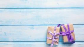 2 праздничных подарочной коробки с настоящими моментами на голубой деревянной предпосылке Стоковое Изображение