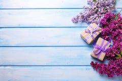 2 праздничных подарочные коробки и цветка llilac на голубом деревянном backgr Стоковая Фотография