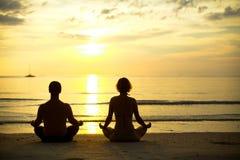 Практика йоги, молодая пара сидя на пляже Стоковые Фото
