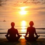 Практика йоги, молодая пара сидя на пляже Стоковое Изображение RF