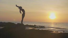 Практика йоги силуэта на заходе солнца Женщина Yong делая тренировку йоги на пляже видеоматериал