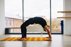 Практика йоги Человек делая представление моста внутри комнаты с панорамными окнами Стоковое фото RF