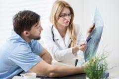 Практикующий врачи смотря изображение рентгеновского снимка Стоковое Изображение
