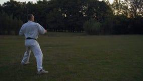 Практикующий врач карате человек в белом кимоно делая комбинации kata рано утром на glade в парке города сток-видео