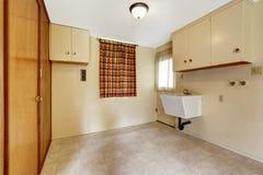 Прачечная с бежевыми стенами и плиточным полом обеспеченный с шкафами и встроенным шкафом Стоковое фото RF