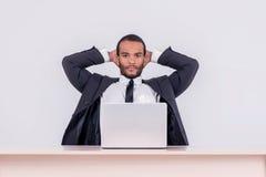 Пребывание в работе Усмехаясь африканский бизнесмен сидя на таблице a Стоковое Фото