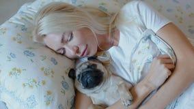 Пребывание женщины в кровати с мопсом щенка