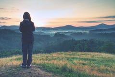 Пребывание молодой женщины на золотом луге и наблюдать к восходу солнца над туманом стоковая фотография