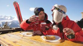 Пребывание на лыжном курорте Пара лыжников имея обед на ресторане поверх горы Человек и женщина держат теплый видеоматериал