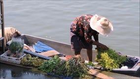 Пребывание пожилой женщины на ее шлюпке и продает некоторый местный овощ и пук банана, около пристани в Таиланде сток-видео