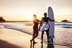 Пребывание серферов пар на пляже океана захода солнца Стоковые Изображения RF