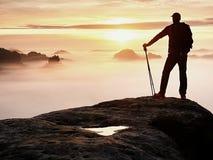 Пребывание силуэта человека на остром пике утеса Удовлетворяйте hiker насладитесь взглядом Высокорослый человек на скалистой скал стоковая фотография