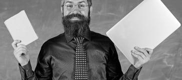 Пребывание современное с технологией Битник учителя бородатый держит книгу и компьтер-книжку Выберите правый метод обучения учите стоковое изображение