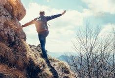 Пребывание человека альпиниста на краю глубоко с взглядом на горе v Стоковые Изображения RF
