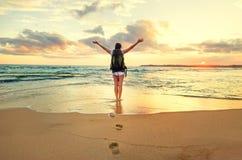 Пребывание backpacker женщины на линии прибоя океана на времени захода солнца стоковое изображение